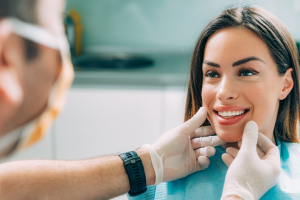 A dentist examines the teeth of a smiling woman
