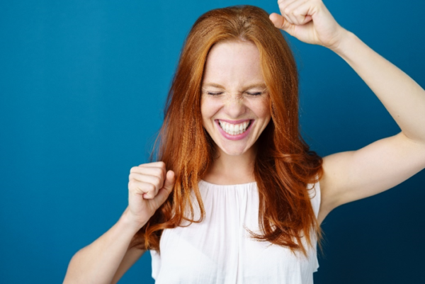 A smiling redheaded woman raises her arms in celebration in front of a blue background