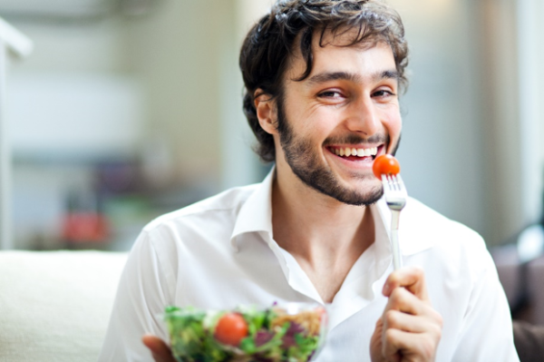 A bearded man with dark hair smiles into the camera while eating a tomato out of a salad