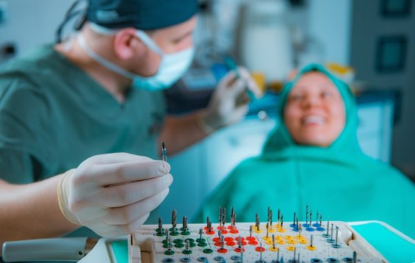 A dentist prepares to use a series of tools of a female patient