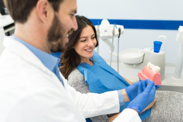 A dentist shows his female patient a model of teeth and gums
