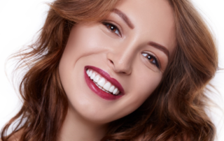 a beautiful woman with brown hair, red lips, brown eyes, and white teeth smiling.