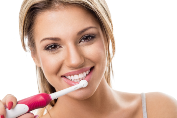A pretty woman with pink lips and white teeth seems super stoked to be brushing her bottom lip instead of her teeth with a red electric toothbrush.